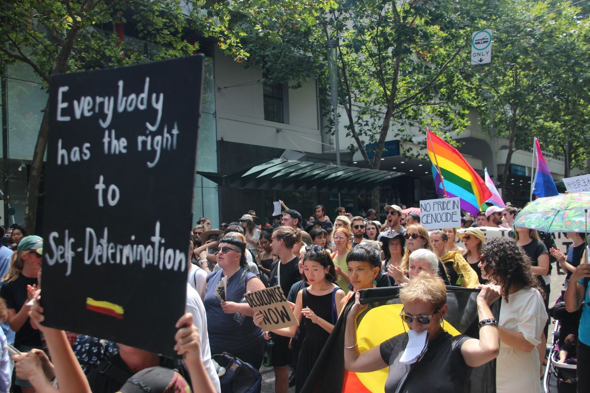 Invasion Day / Survival Day March participant holds sign 'everybody has the right to self determination'
