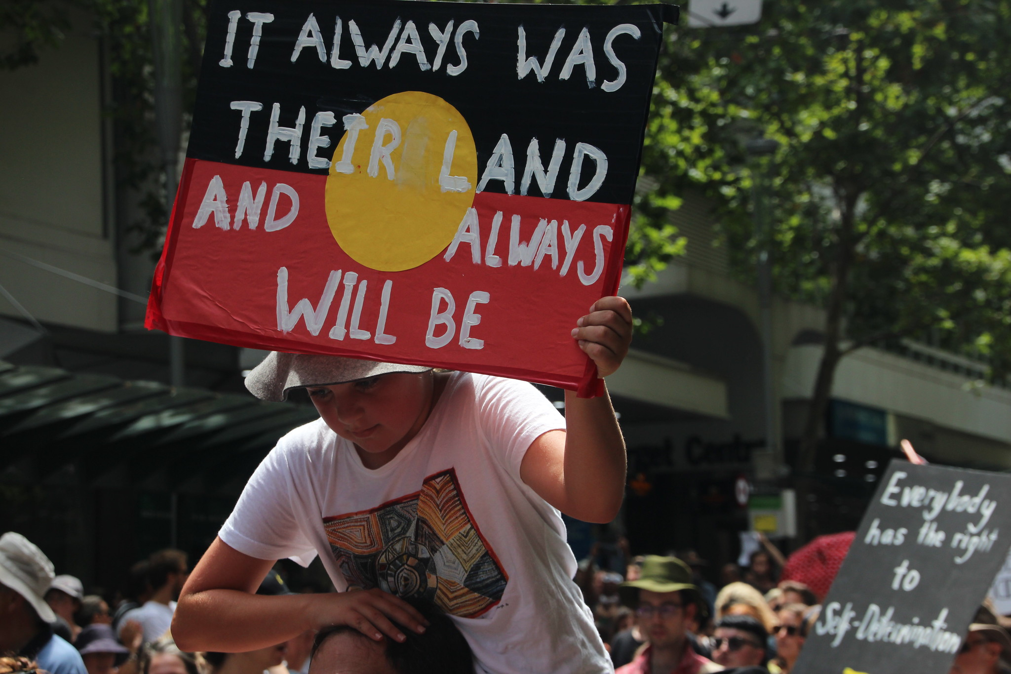protester with sign saying 'it always was their land and always will be'.