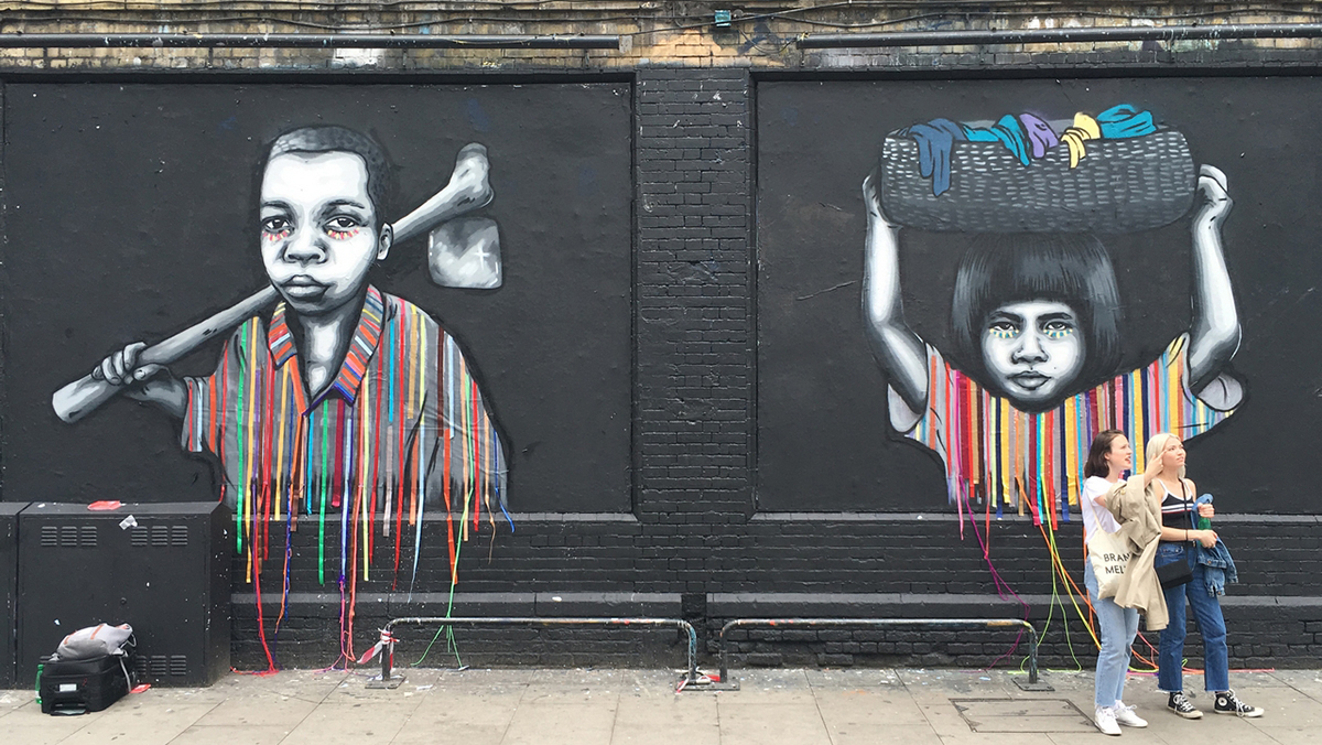 Paintings on a black brick wall of two children holding farm equipment and a bucket of water on their head