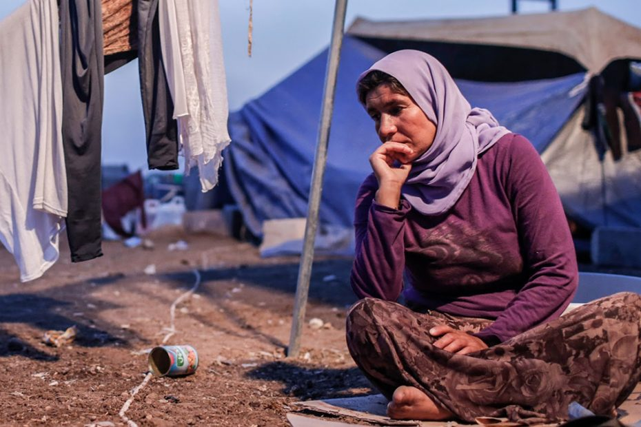 Woman sits outside tent at refugee camp
